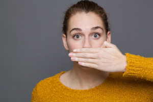 Causes of bad breath, woman covering her mouth in surprise