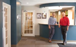 Dr. Schumacher and Dr. Bauer standing at the front desk of Schumacher & Bauer, DDS