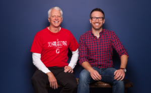 Photo of Dr. Schumacher sitting with Dr. Bauer, Dr. Schumacher in a red The Ohio State University shirt, Dr. Bauer in a red plaid shirt with a dark blue background