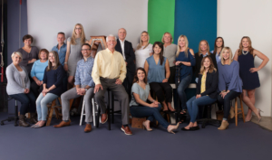Team photo from the Schumacher & Bauer, DDS team in front of white, green and blue background in a studio