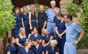 Schumacher & Bauer team photo, everyone in scrubs laughing outside with trees and bricks behind them