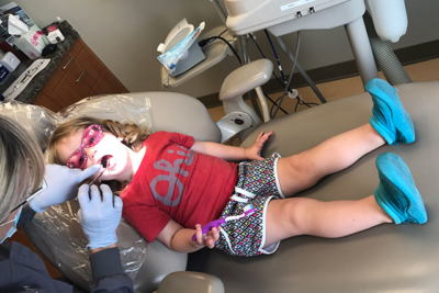 Child in chair in dentist office with a dental hygienist