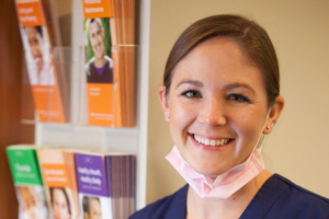 Photo of Kristi of Schumacher & Bauer smiling, featured image for a post about causes of cavities
