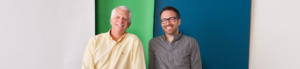 Photo of Dr. Schumacher and Dr. Bauer together with a white, blue and green backdrop
