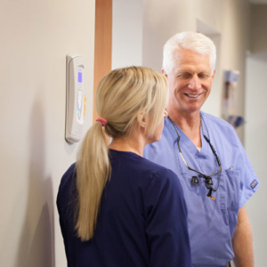 Dr. Schumacher discussing dental laser treatments with his staff