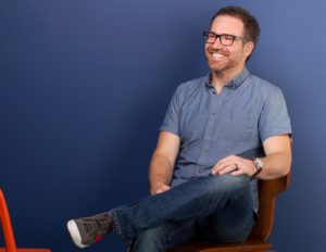 Dr. Bauer, sitting and smiling with a dark blue background