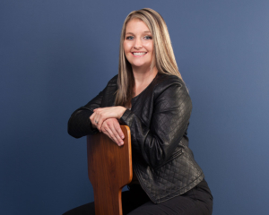 Headshot of Heather Tabor at Schumacher and Bauer in Columbus OH, wearing a black jacket, sitting on a brown chair with a blue background