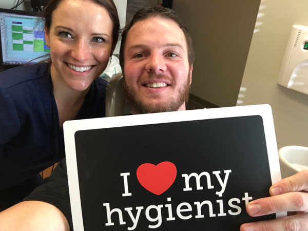 Patient of Schumacher & Bauer holding a sign that says I heart my hygienist