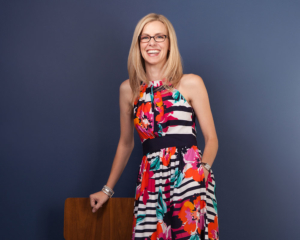 Photo of Kelly, the Schumacher & Bauer Practice Manager, wearing a colorful dress, leaning on a chair in front of a blue background