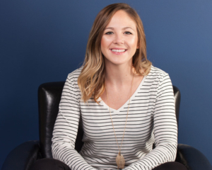 Headshot of Kristi Lynch, Dental Assistant at Schumacher and Bauer in Columbus, wearing a striped shirt on a blue background while sitting in a brown chair