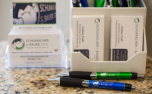 Pens and business cards at the Schumacher & Bauer front desk, where you can ask about Invisalign