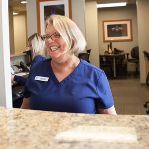 Heidi laughing at the front desk at Schumacher & Bauer, DDS