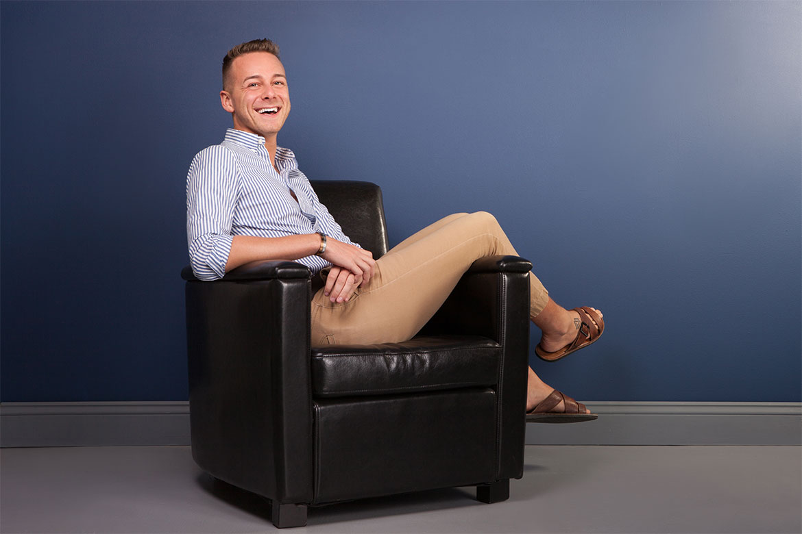 Thoughts from a male dental hygienist, Jake Hanley, photo of Jake smiling in a leather chair