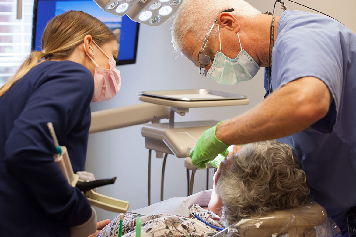 Teeth grinding, dentist and hygienist helping a patient in her chair