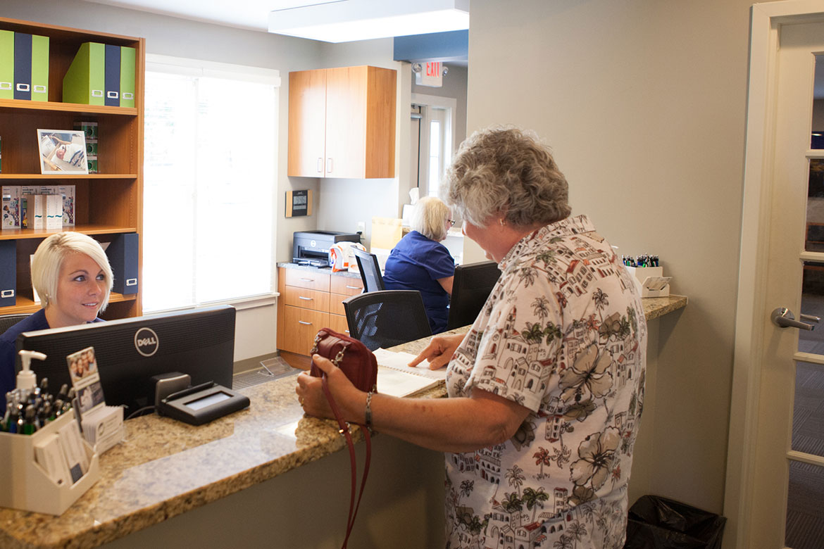 Dental insurance benefits, photo of Aly and patient at the front desk