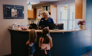 Heidi with two young patients at Schumacher Bauer front desk