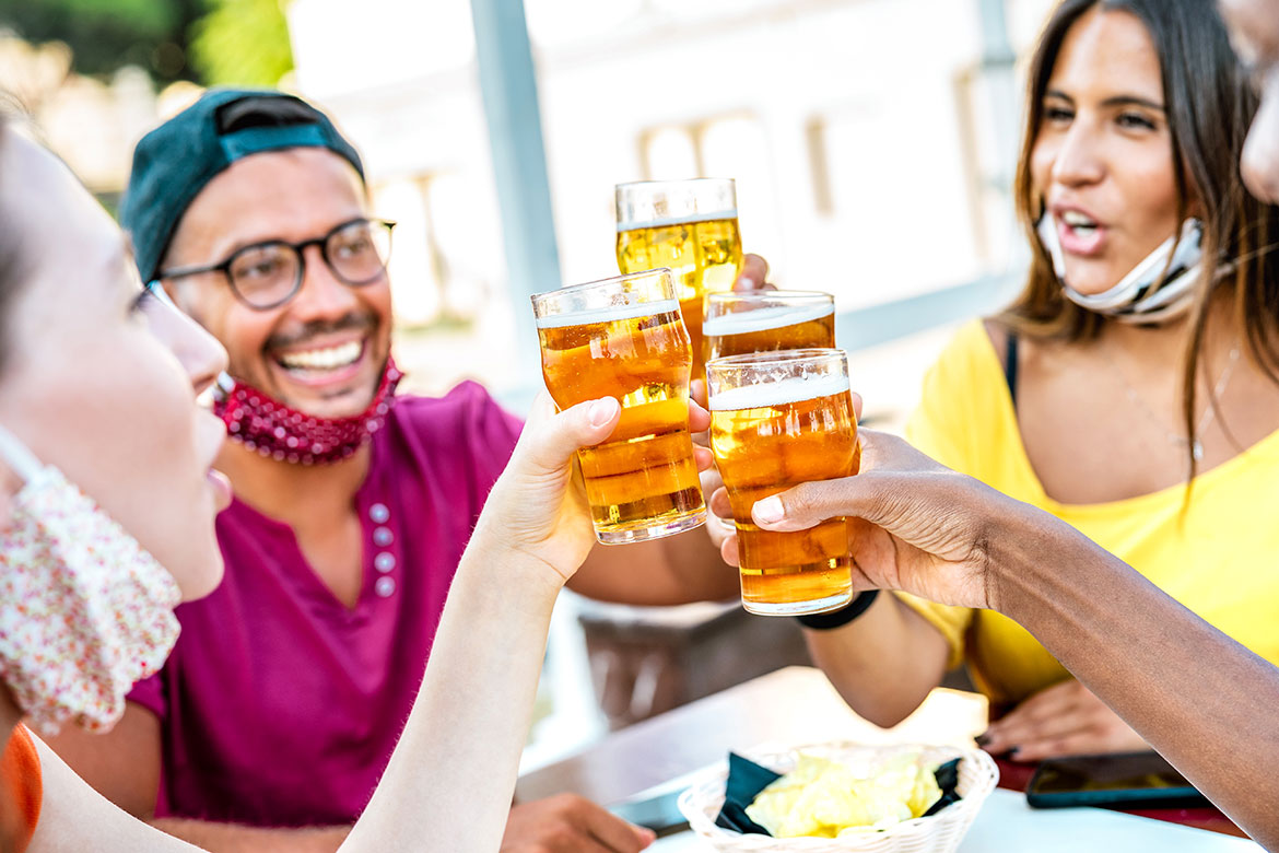 Group of friends cheersing with pints and masks to celebrate that beer benefits dental health